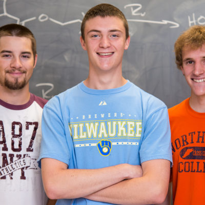 Three Northland College chemistry students standing in front of chalkboard.