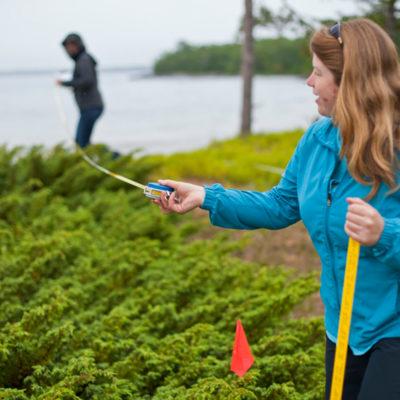 Professor Sarah Johnson holds measuring tape at Stockton Island