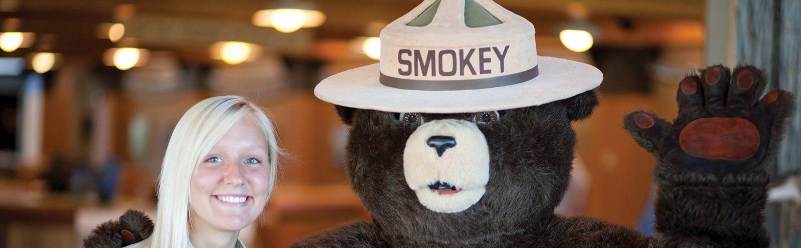 girl posing with Smokey the Bear