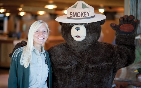 girl posing with Smokey the Bear