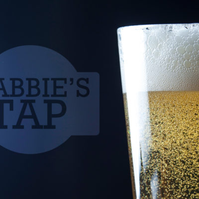 Glass of beer sitting next to Cabbie's Tap logo.