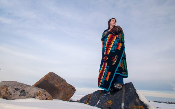 Northland College student standing on rock at Lake Superior