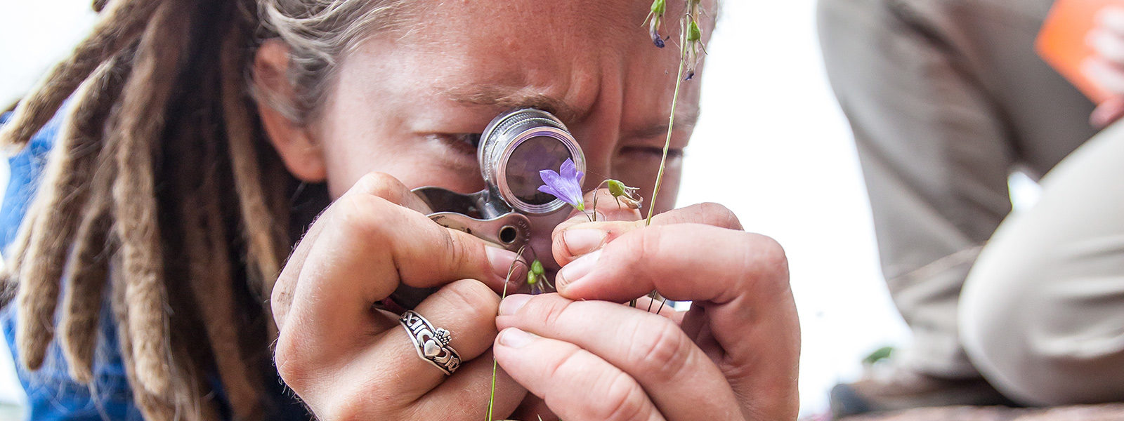 Northland College student looking through magnifying glass