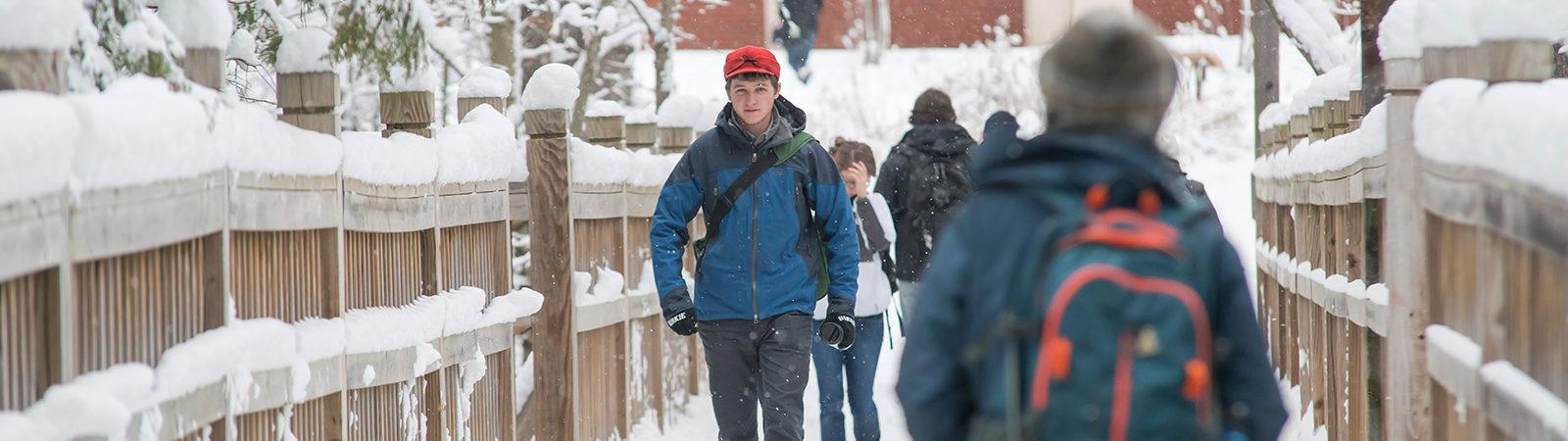 Students walking on bridge in winter.