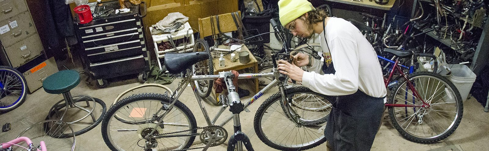 Northland College student working on bike.