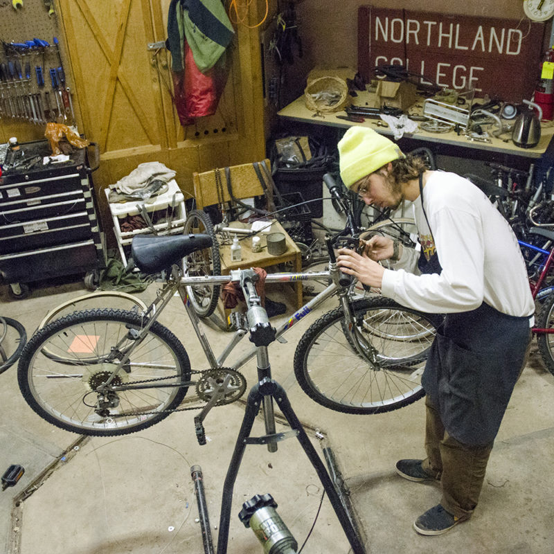 Northland College student working on bike.