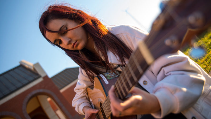 Northland College student Hattie Hoffman plays guitar