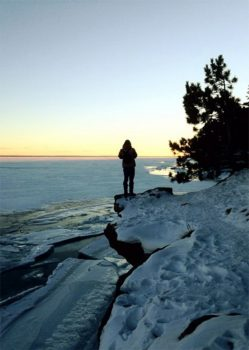 Northland College student standing on shore of Lake Superior