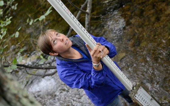 Northland College student Kim Oldenborg measures water on a stream.