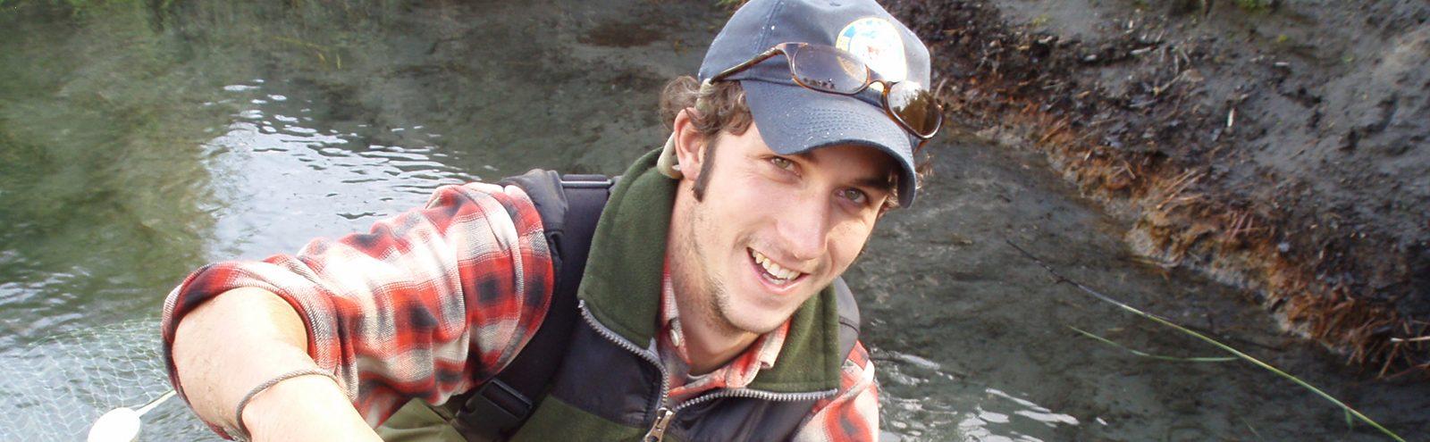Northland alum fish geneticist holds up fish