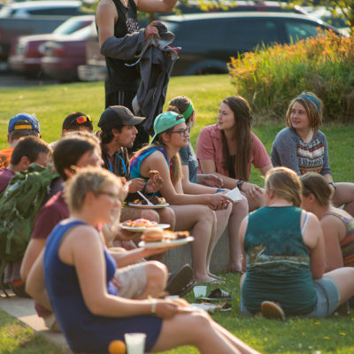 Students sit outside with plates of food.