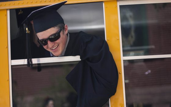 Student in commencement gown on bus