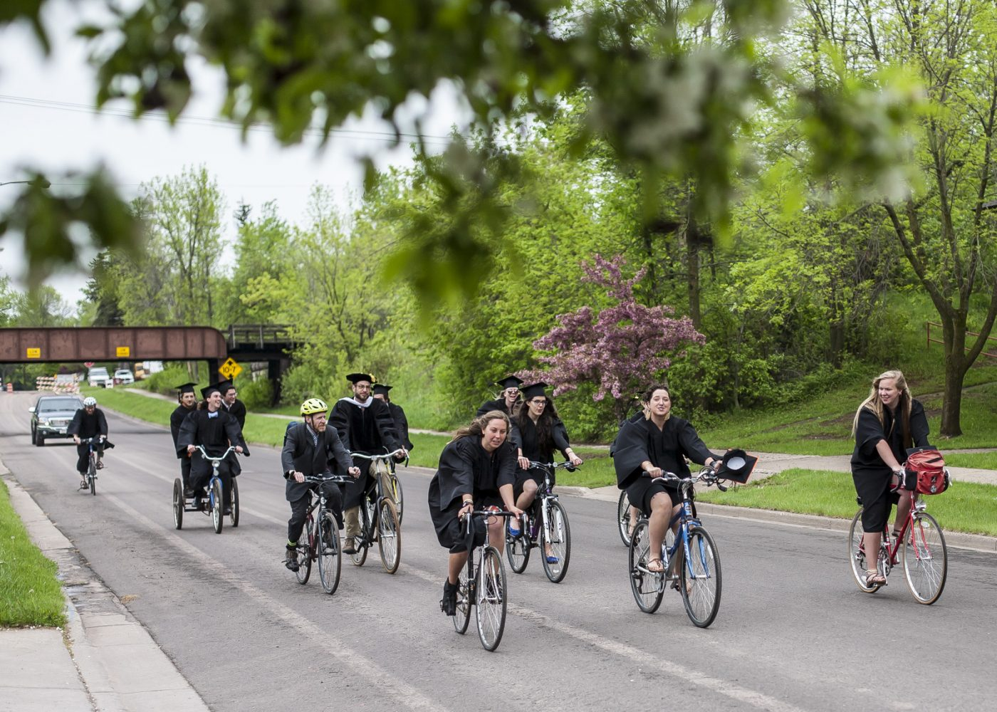 Students bike on street in cap and gown