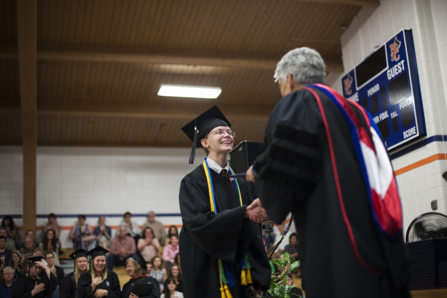 president shaking hands with student at commencement