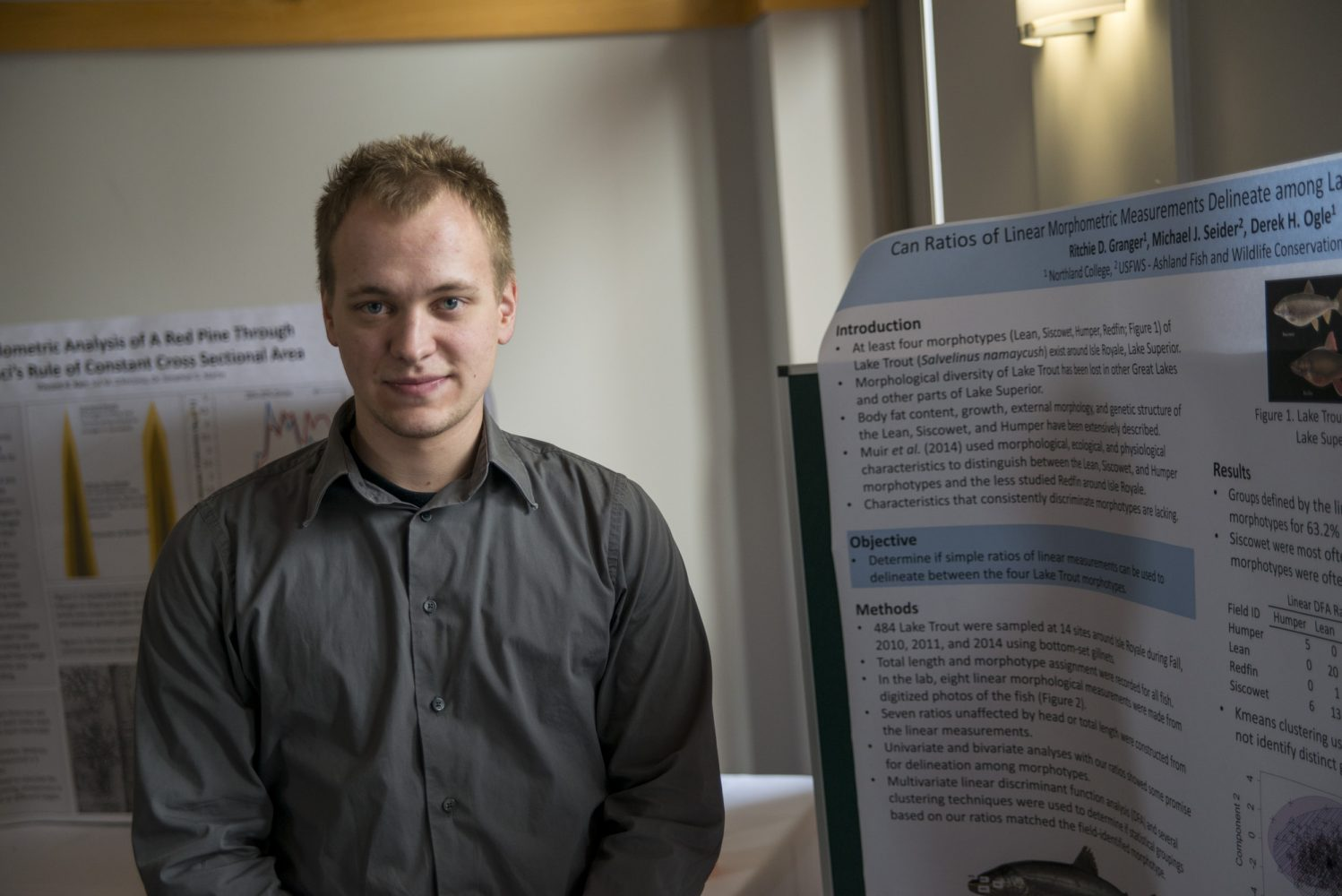 Northland College student stands before his poster presentation.