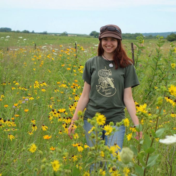 Northland College student standing in prairie.