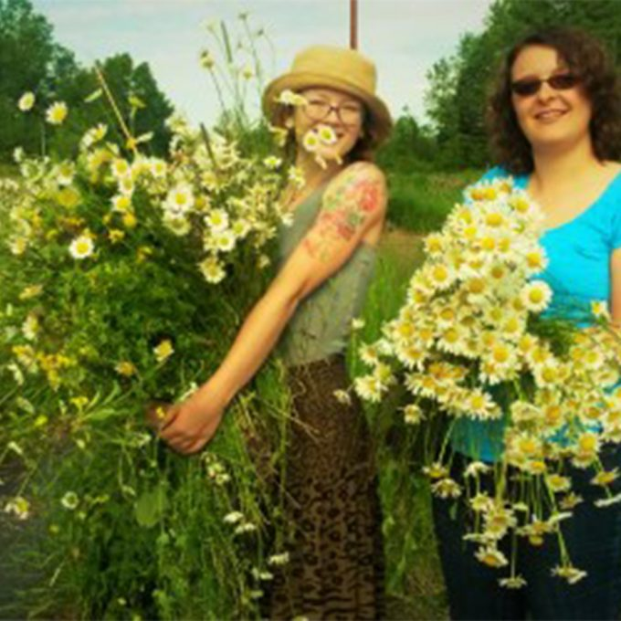 Two Northland College students stand with flowers in their hands.