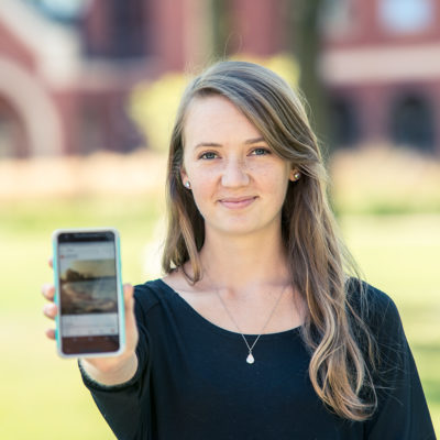 Northland College student holding phone.