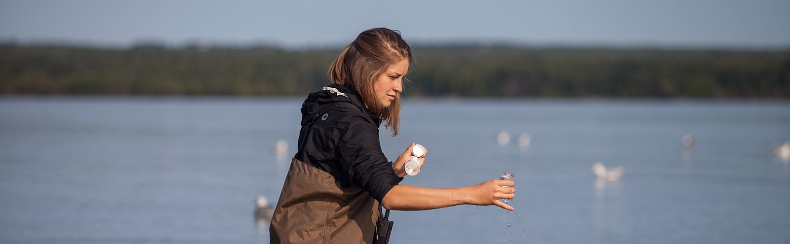 Northland College student taking a water sample.
