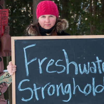 Mary Dougherty holding chalkboard that says Freshwater Stronghold
