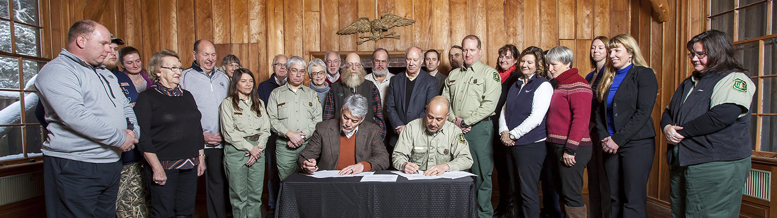 Group shot with Northland College President Michael Miller signing document alongside U.S. Forest Service