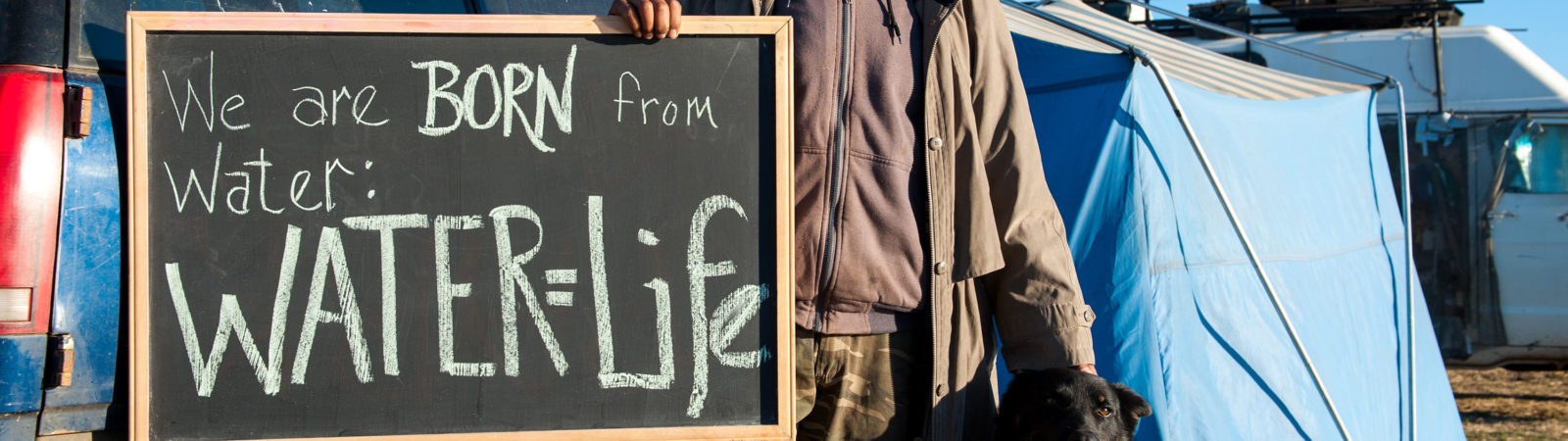 Man standing with chalkboard with the words, Water=Life