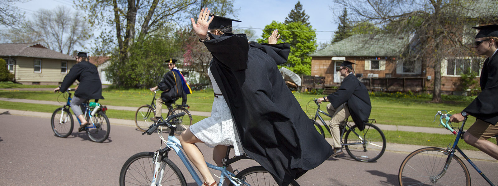 Graduate riding a bike with no hands
