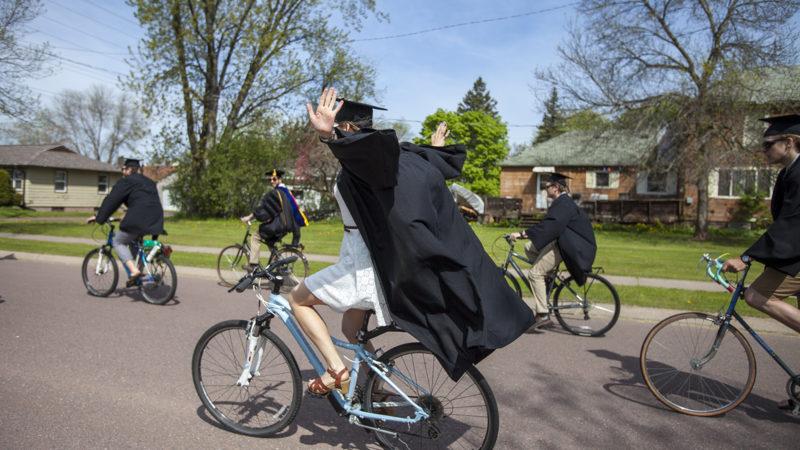 Graduate riding a bike with no hands