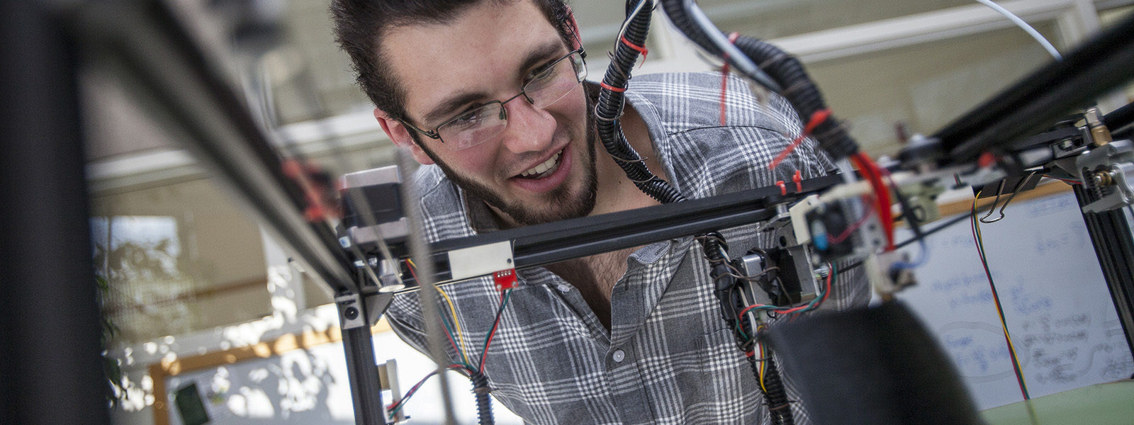 Northland College engineering student working on 3D printer