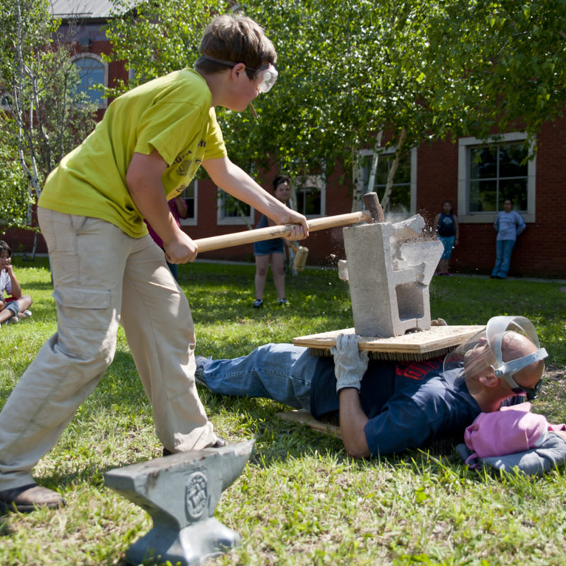 Student breaking a brick on the chest of a teacher laying on a bed of nails