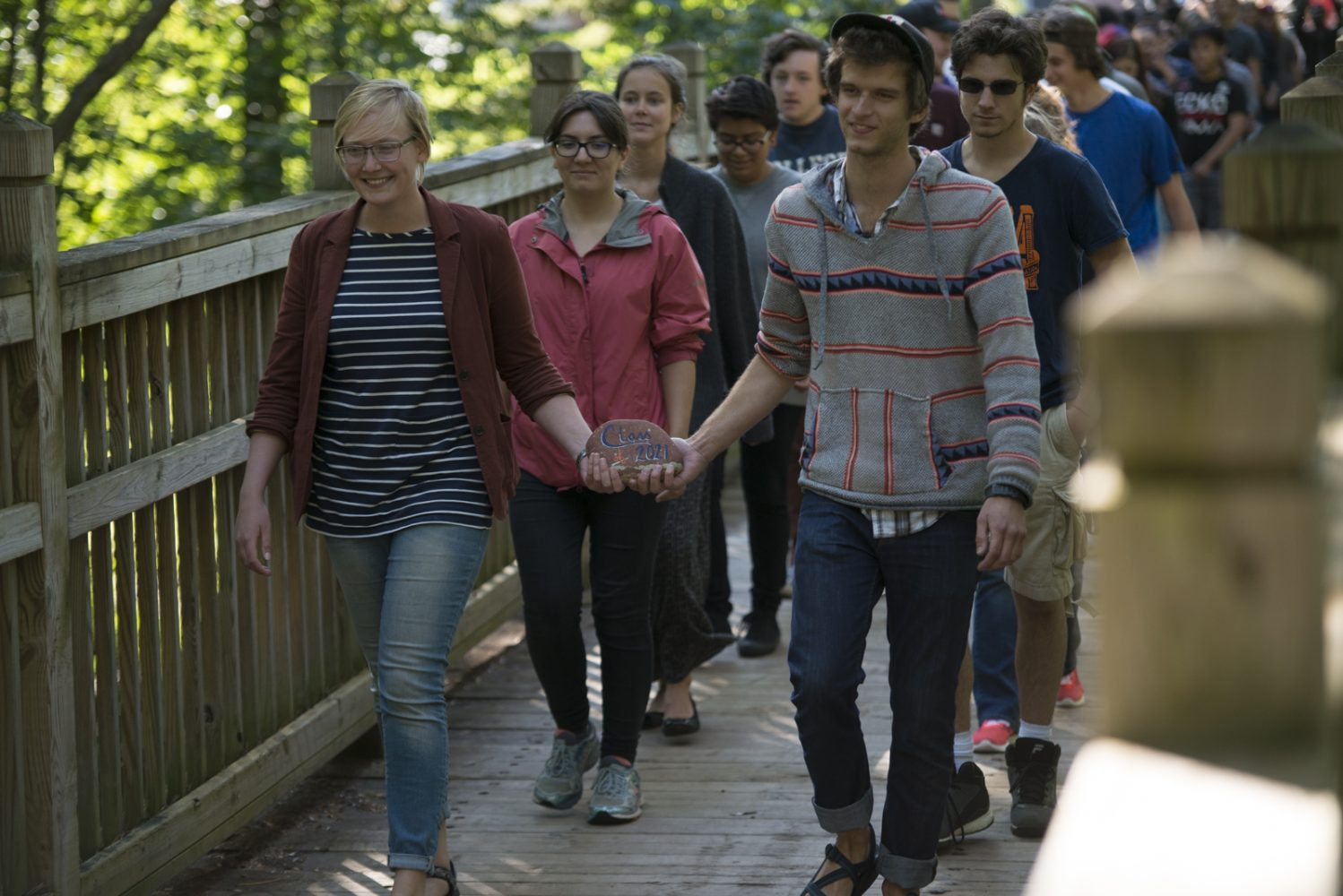 Northland College graduates carry the Class of 2021 rock across the bridge as part of convocation.