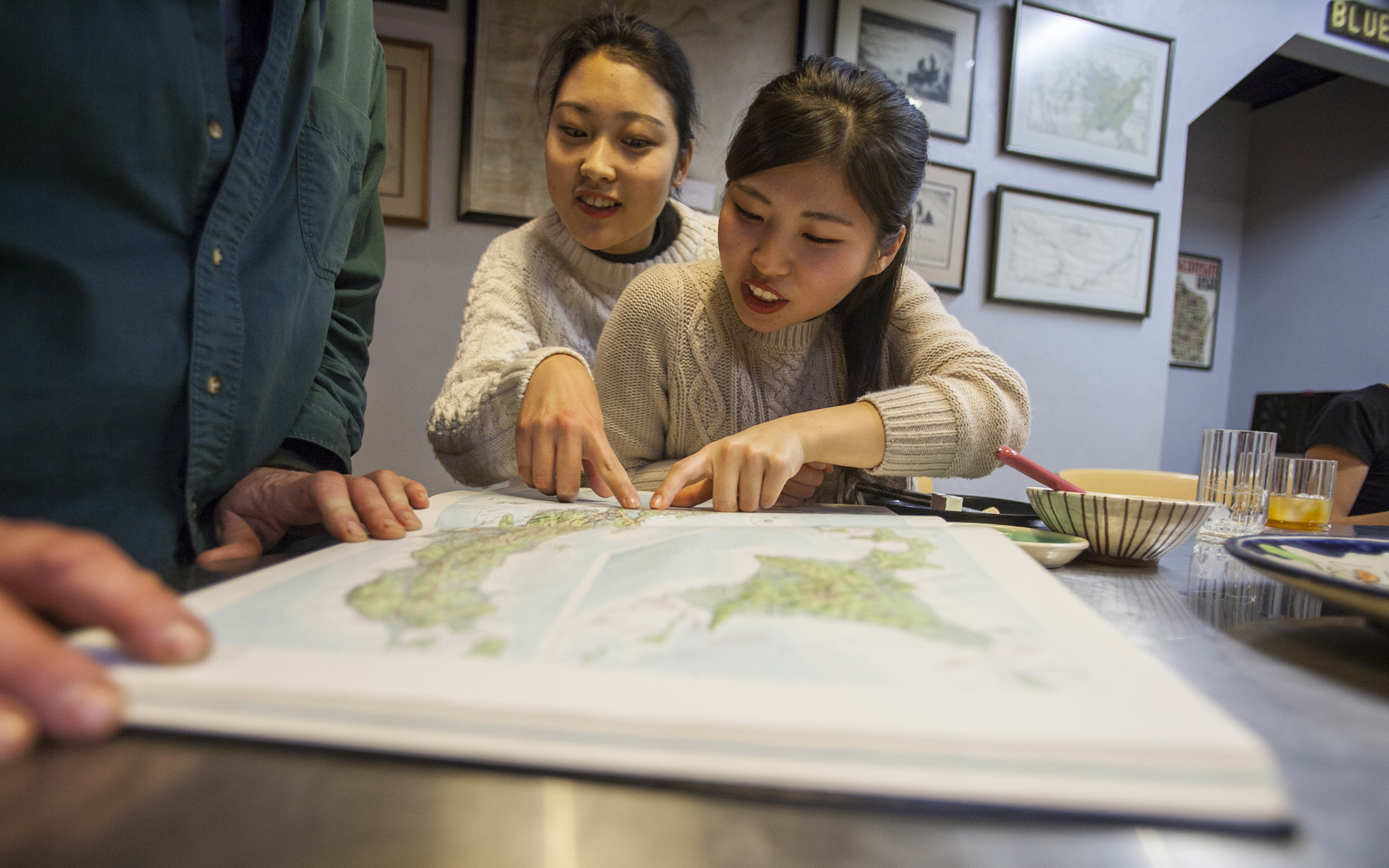 Northland College Japanese exchange students point out their home cities on a map