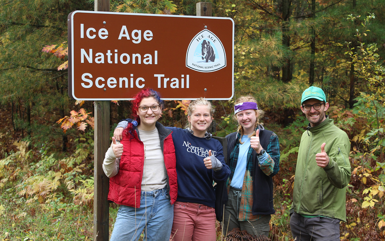 Northland College Students and Professor Dave Ullman pose for a portrait by the Ice Age National Scenic Trail sign.