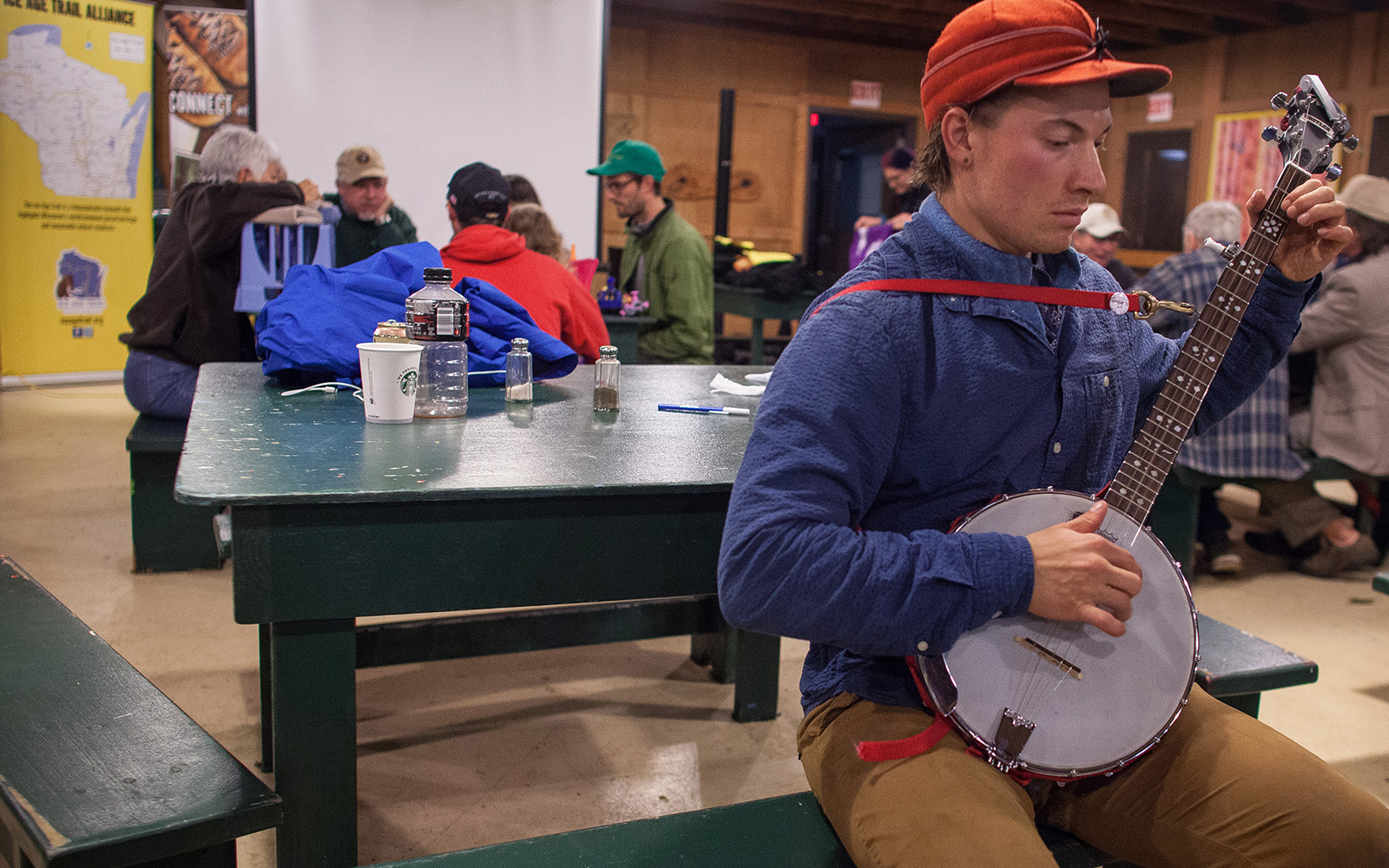 Northland College student plays banjo during a break from building Ice Age Trail.