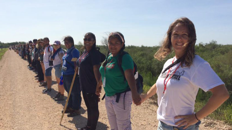 Northland College alumnus Tiffany Kirsten stands with fellow activists along the border of Texas and Mexico