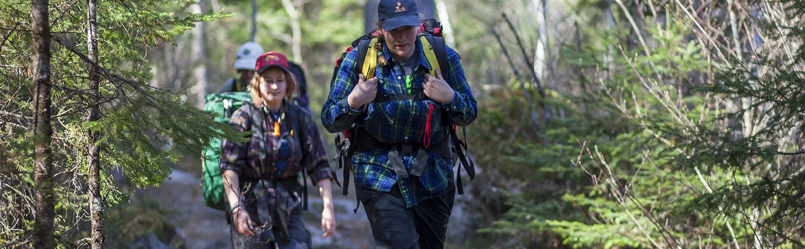 Students backpacking on a trail.