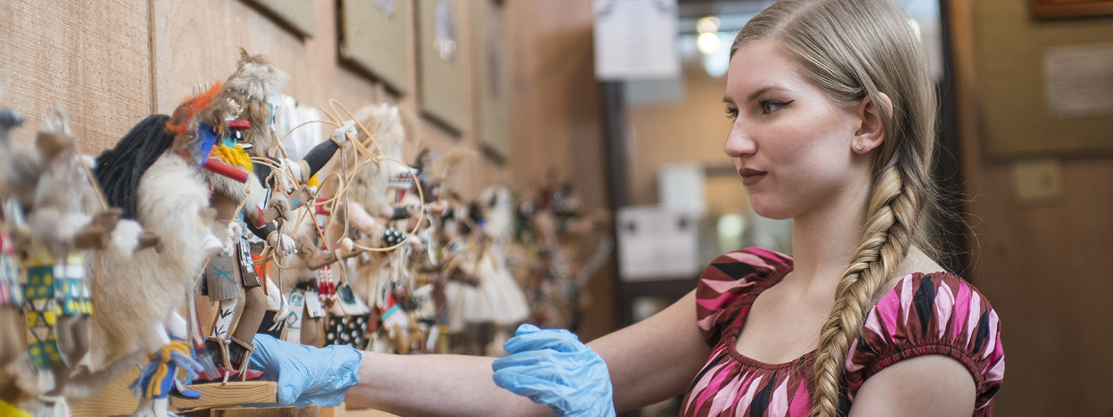 Northland College student Isa Meyer works with a display in the Native American Museum
