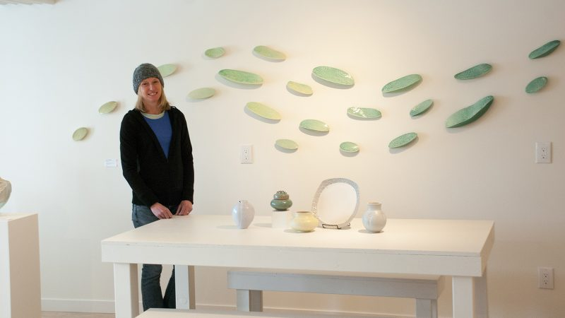 Northland College alum Julie Anderson poses with sculptures.