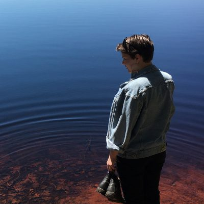 Northland College alum Kinsey Neal standing in Lake Superior