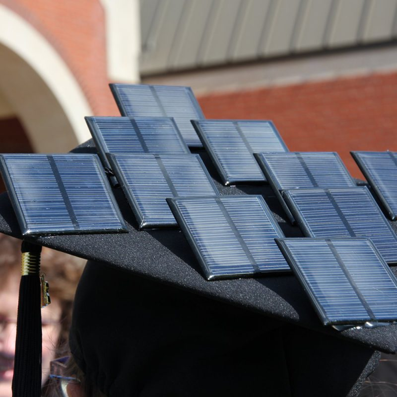 Northland College graduate Laura Loucks with solar panels on her graduation cap at commencement