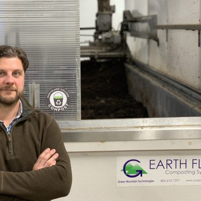 Northland College Food Center Director Todd Rothe stands in front of the composting machine.