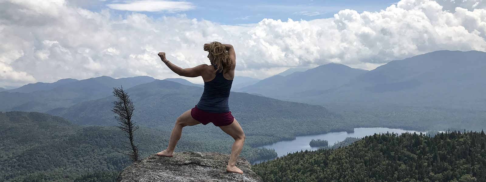 Northland College alum Kayte Meola in warrior pose on mountain top.