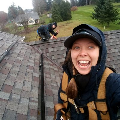 Northland College alum Audra (Jung) Willing installing solar panels on top of a roof.