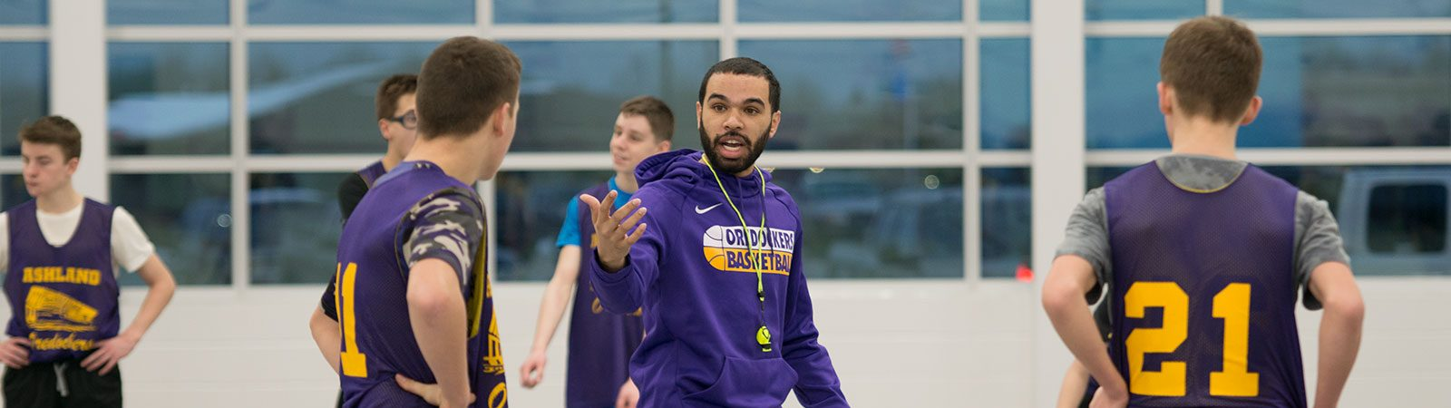 Northland College student Danon Briggs coaching kids on the basketball court.
