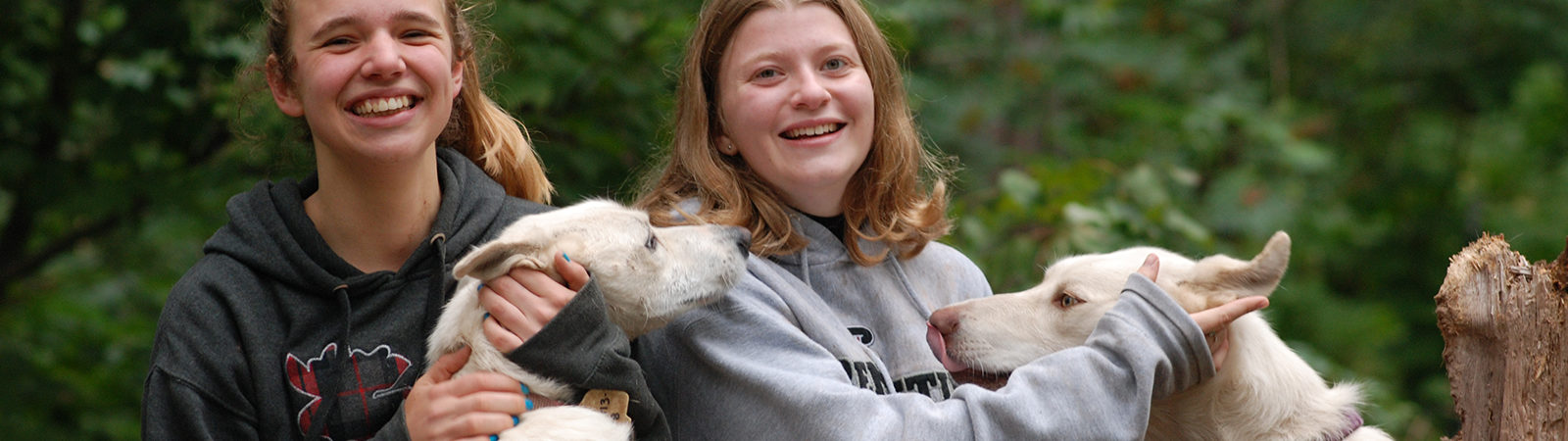 Two Northland College students and dogs