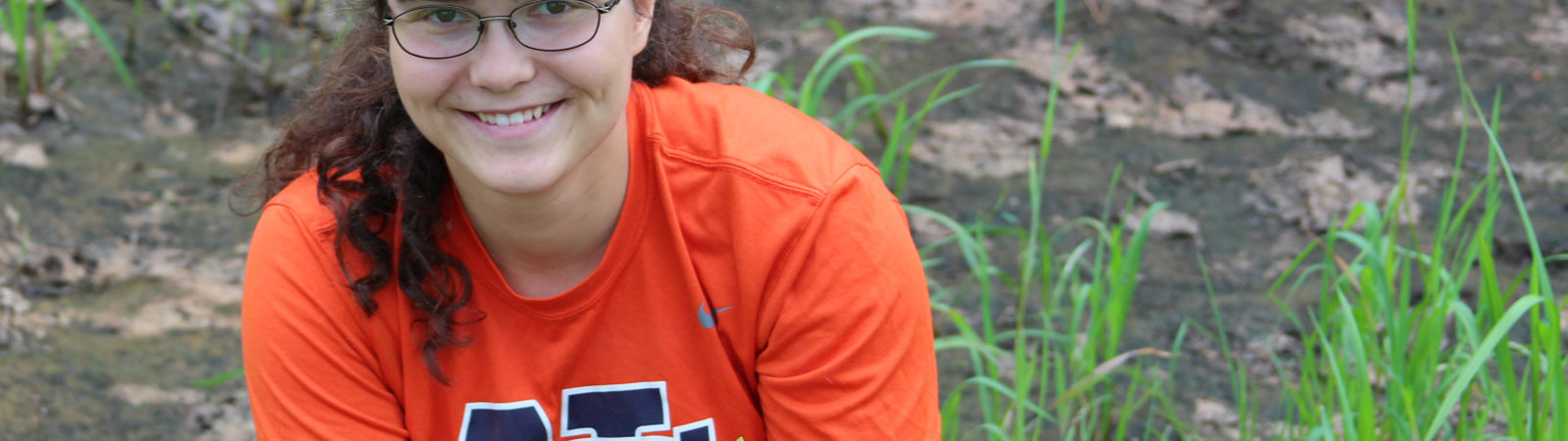 Northland College student Erin Bergen assists with planting a native garden.