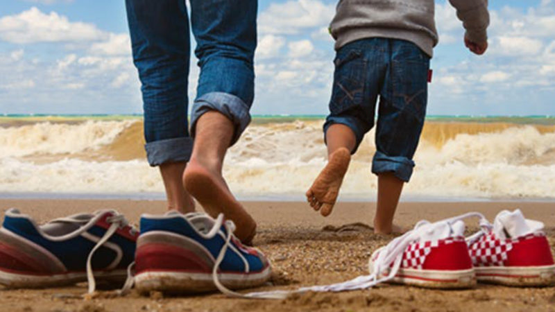 Family running into the waves with their shoes on the beach