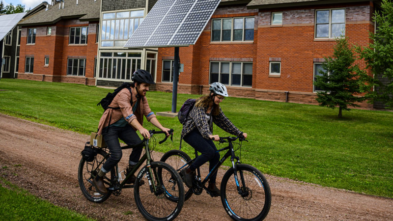 Two Northland College students biking past solar panels