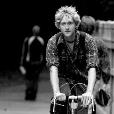 Black and white photo of student biking on bridge