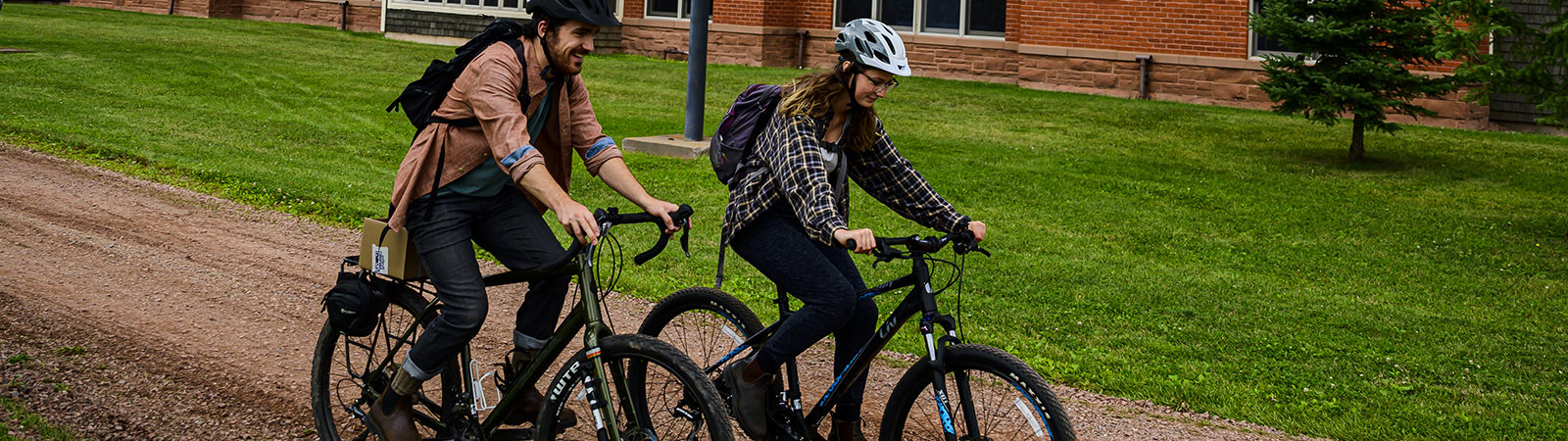 Northland College students ride bikes past solar panels
